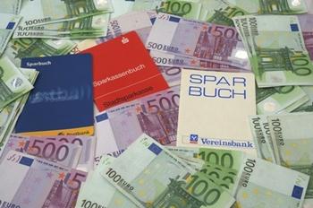 Das Bild zeigt Sparbücher und Geld.